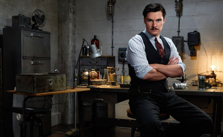 A promotional shot of the guy playing the mad scientist sitting with his arms crossed in a makeshift lab