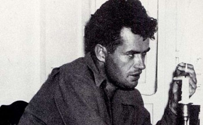 Jack Parsons sitting at a table with a lit candle in front of him