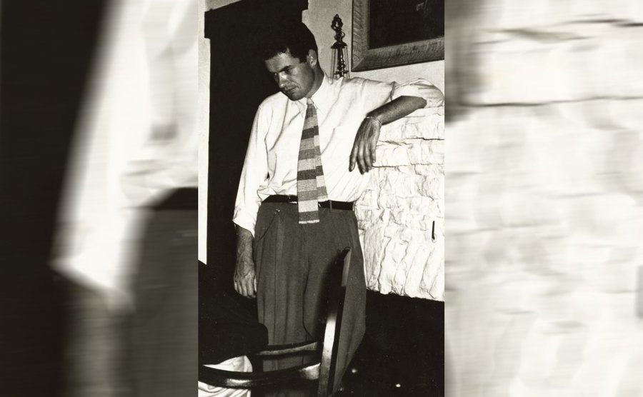 Jack Parsons leaning up against a fireplace ledge