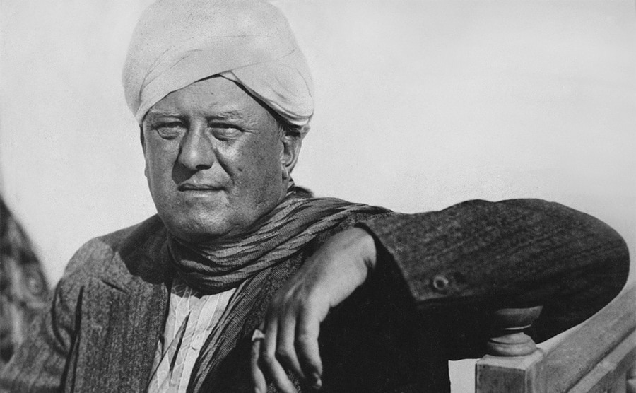 Aleister Crowley posing in a white turban leaning on a banister