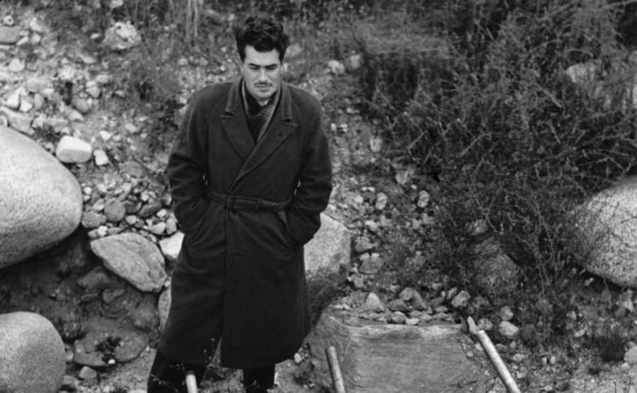 Jack Parsons standing in a trench coat in front of a large tube with poles tied to it