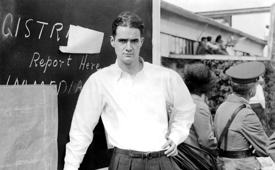 Howard Hughes posing in front of a blackboard