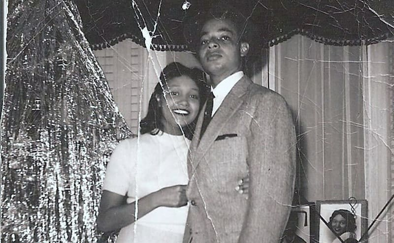 A happy black couple from the 50s posing in front of an old TV set