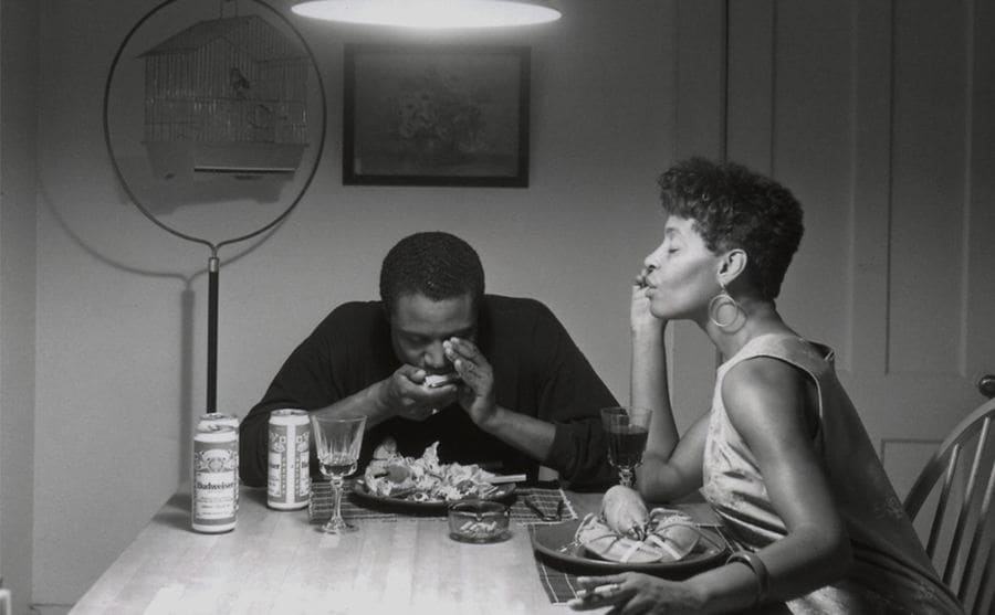 A black couple sitting at a kitchen table together with a meal in front of them
