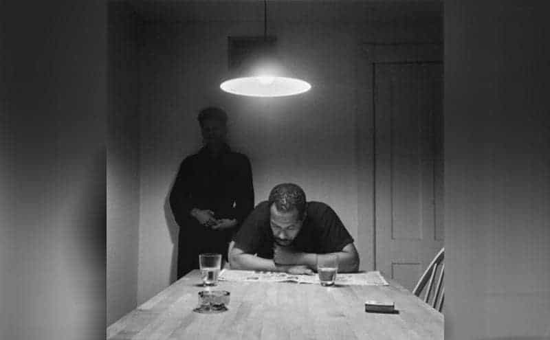 A black couple with the husband sitting at the kitchen table reading a newspaper while she stands behind him against a wall