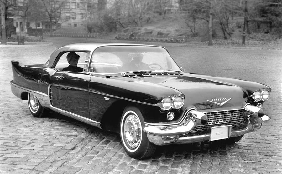 A Cadillac Eldorado broughman in the 1950s parked in a long brick driveway