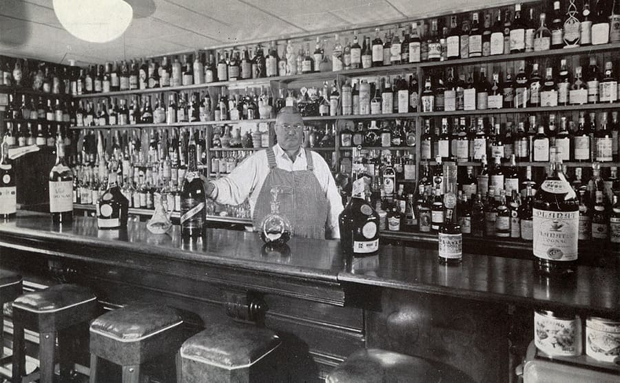 An old bar from the 1950s with a large man behind the counter and shelves full of liquor