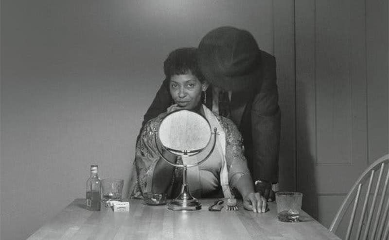 A black couple in the kitchen while the wife sits in front of a mirror doing her make up
