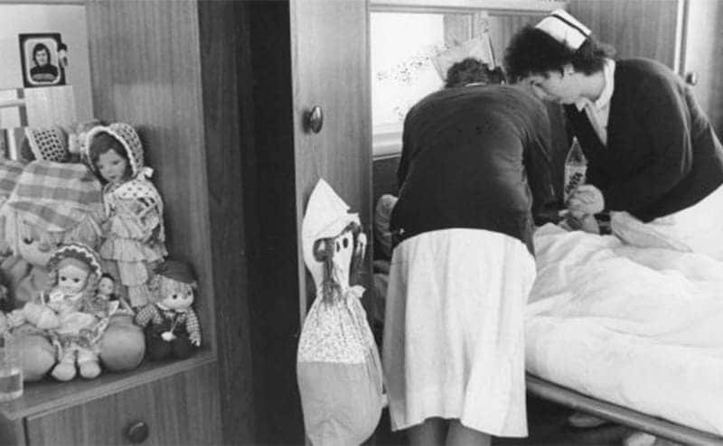 A woman being helped in an asylum in the 50s