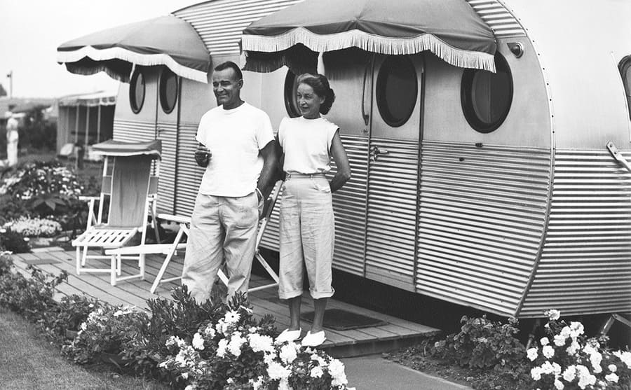 A black couple posing in front of their trailer in the 1950s
