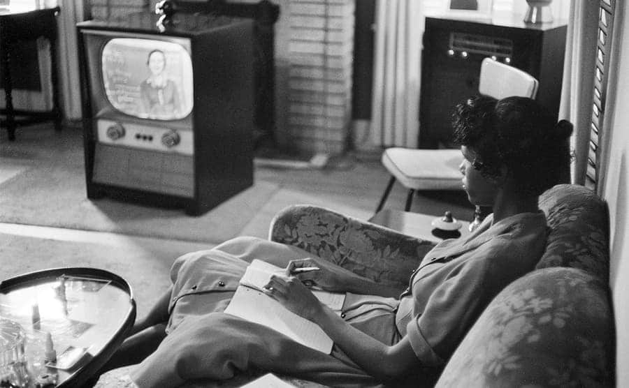 A black woman sitting on a couch watching tv with a notebook in front of her