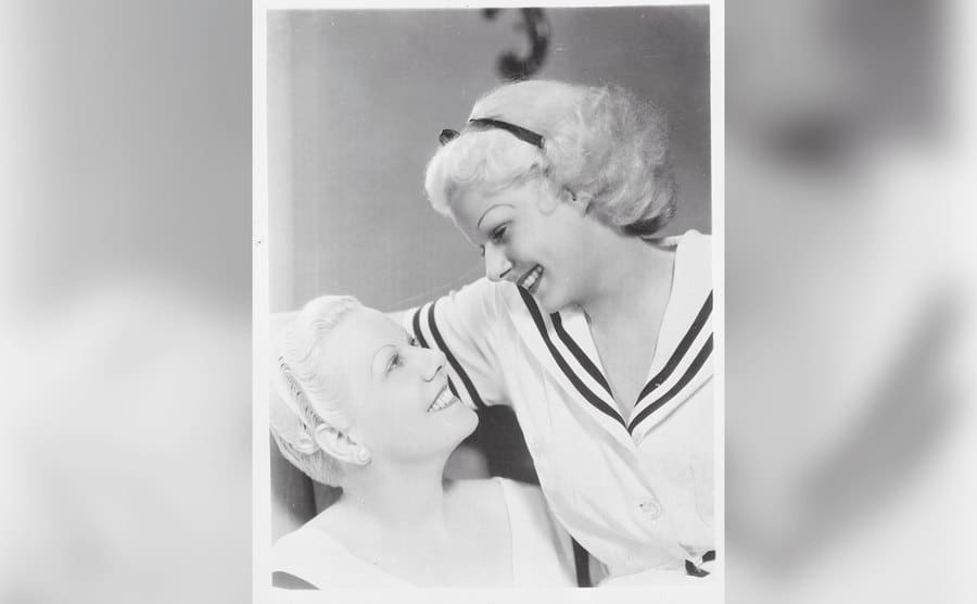 The lovely Jean Harlow and her equally lovely mother staring and smiling at each other.