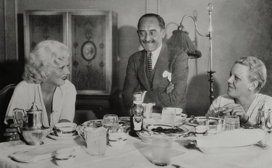 An intimate family scene, like Jean Harlow, famed platinum blonde motion picture player, enjoys breakfast with her parents, Mr. and Mrs. Marino Bello, during a recent trip to San Francisco.