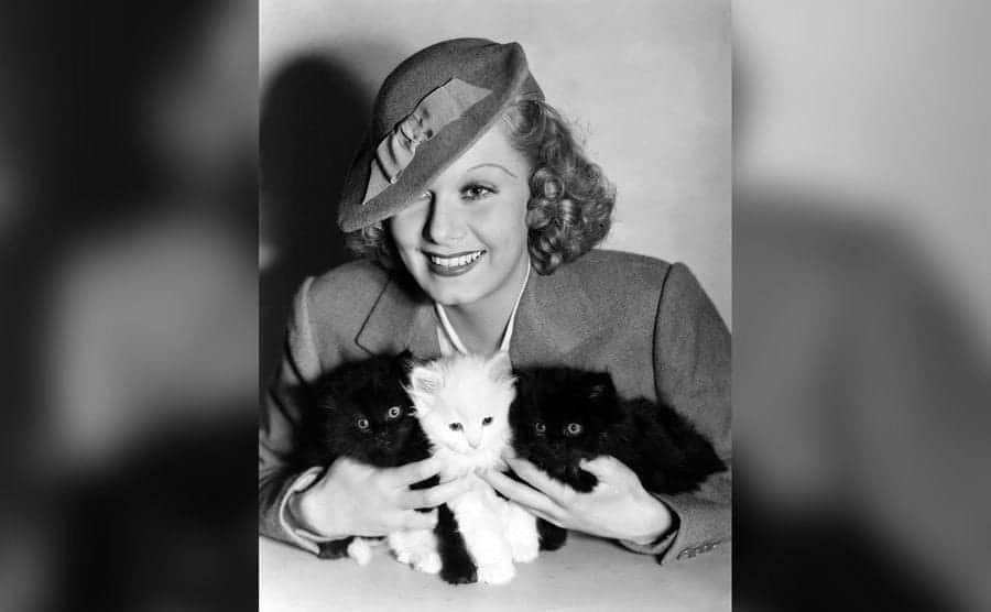 American actress Jean Harlow posing for a photo while holding kittens.