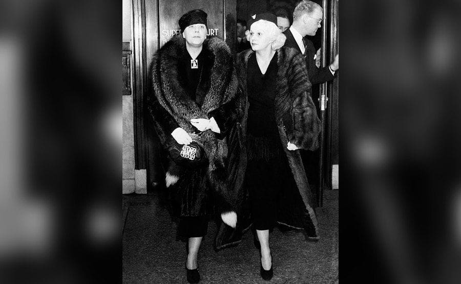 Jean Harlow and her mother walking out of a building in full fur coats, arm in arm.