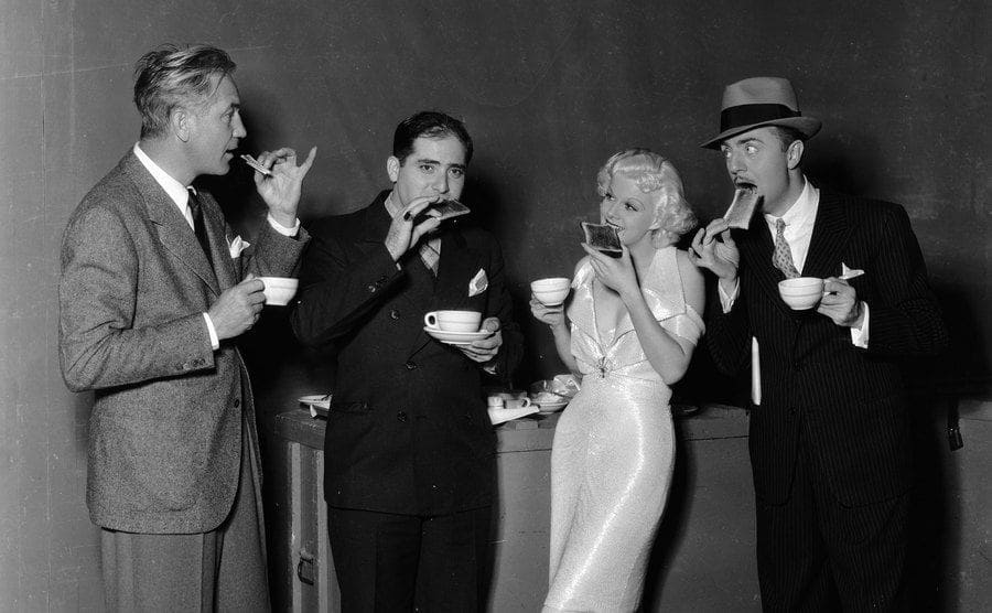 American actress Jean Harlow on the set of the MGM musical melodrama 'Reckless' with director Victor Fleming and co-star William Powell.