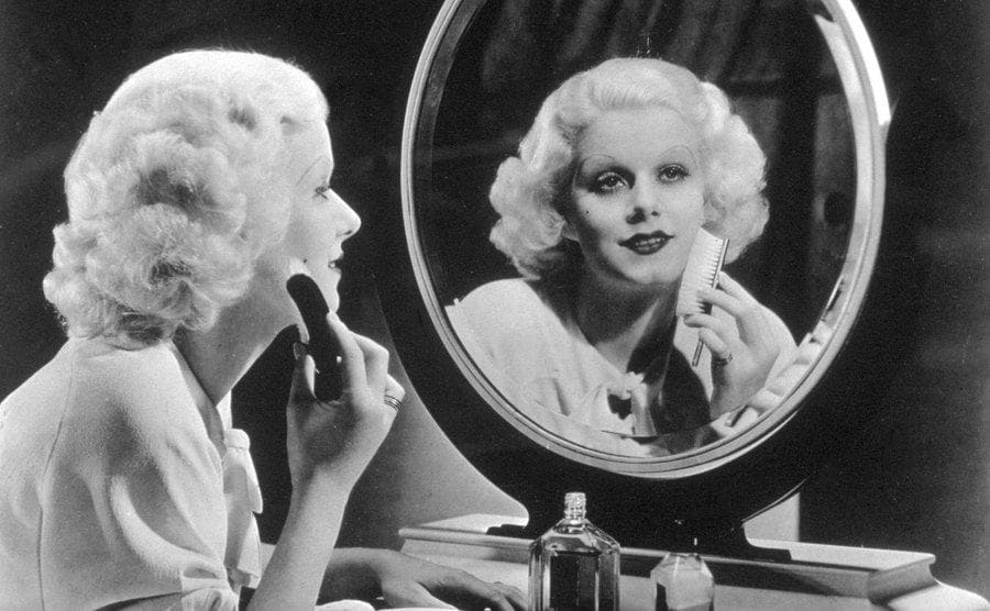 Actress Jean Harlow sitting at her dressing table.