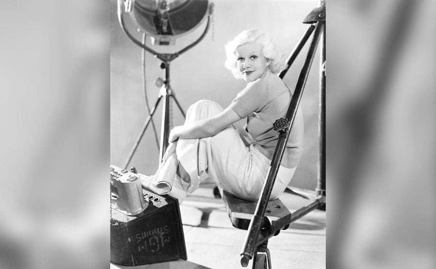 American actress Jean Harlow reading a script on a movie set.