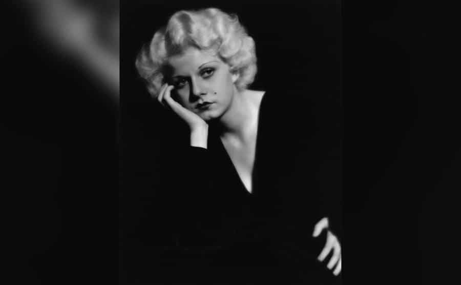 Portrait of Jean Harlow in a pensive pose, wearing a black v-necked dress.