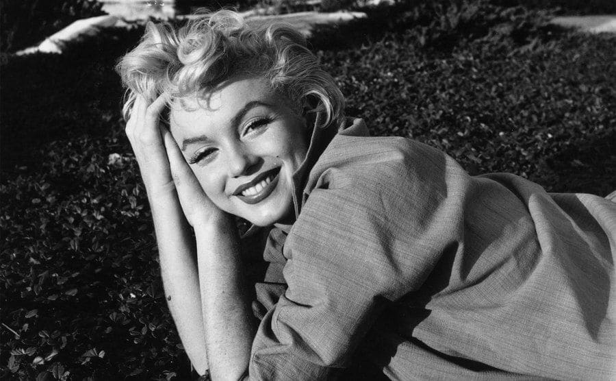 American film star Marilyn Monroe laying on the grass.