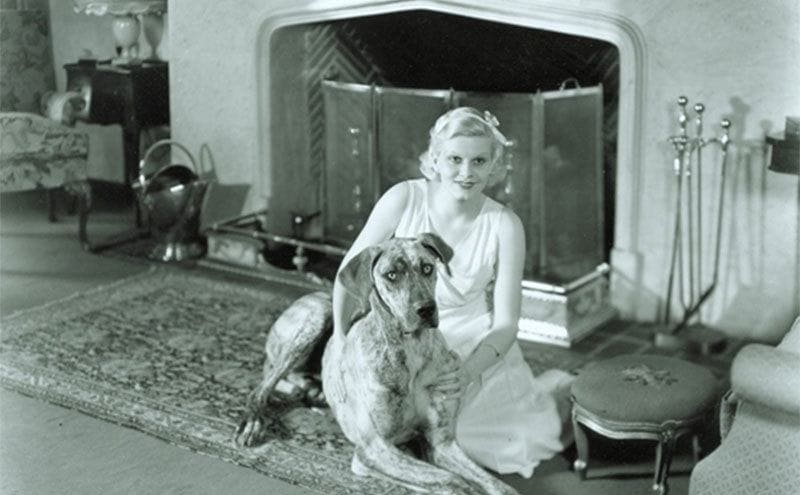 Jean Harlow sitting on the floor beside her fireplace while holding and petting Rin Tin Tin, the dog.