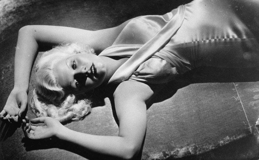 The US-American actress Jean Harlow laying on a bed.