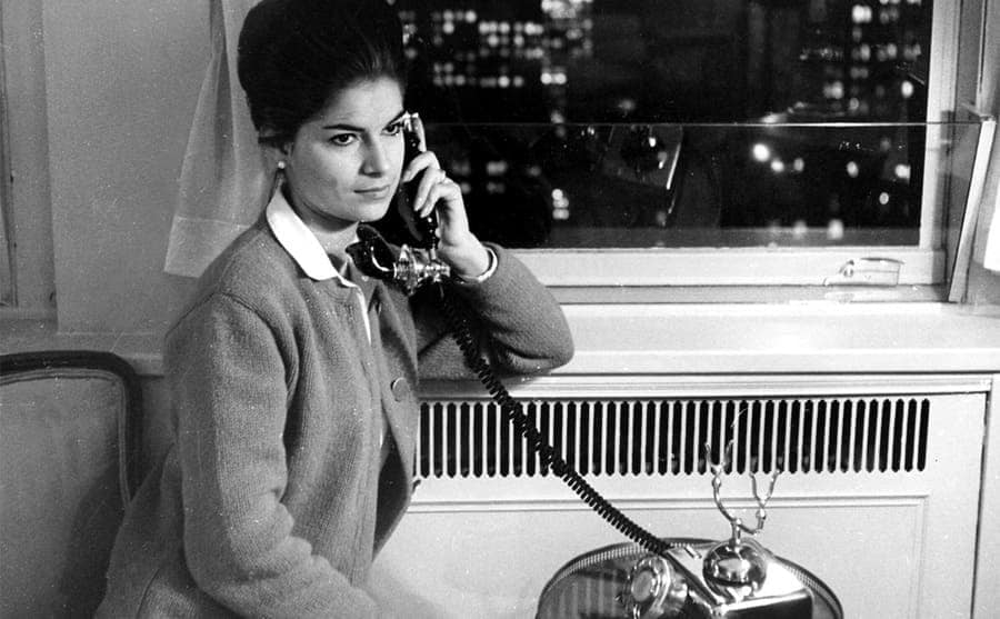A woman talking on the phone near to a window with a view
