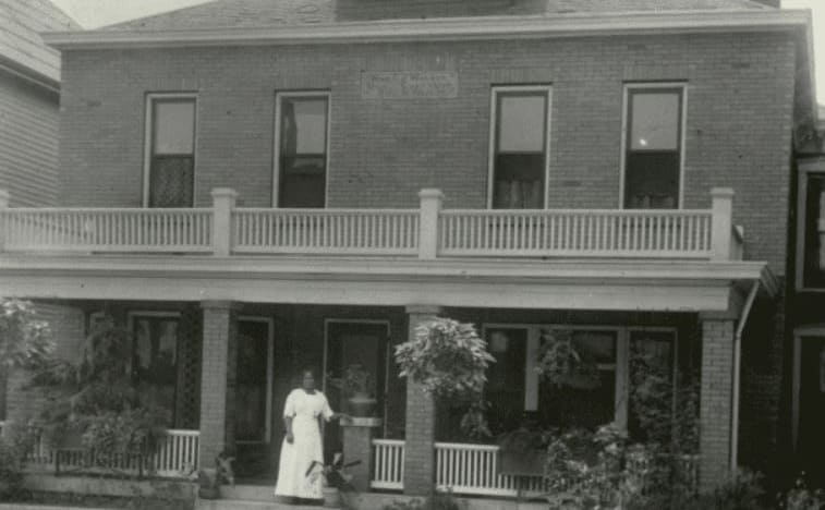 Madam C.J. Walker standing in front of a home in Indianapolis