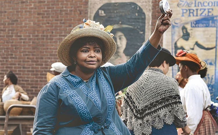 Octavia Spencer as Madam C.J. Walker holding up some product to sell