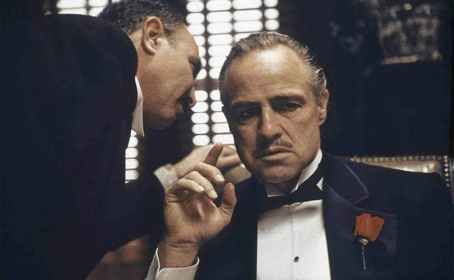 Marlon Brando with someone whispering in his ear from the film The Godfather
