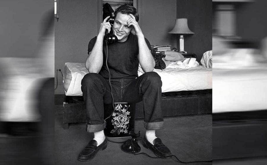 Marlon Brando sitting on a trash can next to his bed while speaking on the telephone circa 1950