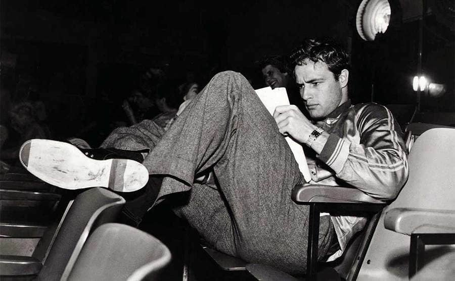Marlon Brando sitting in theater chairs reading a script