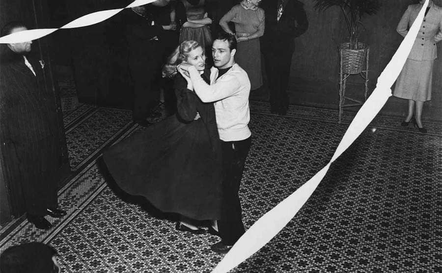 Eva Marie Saint and Marlon Brando dancing on an open dance floor in the film On The Waterfront