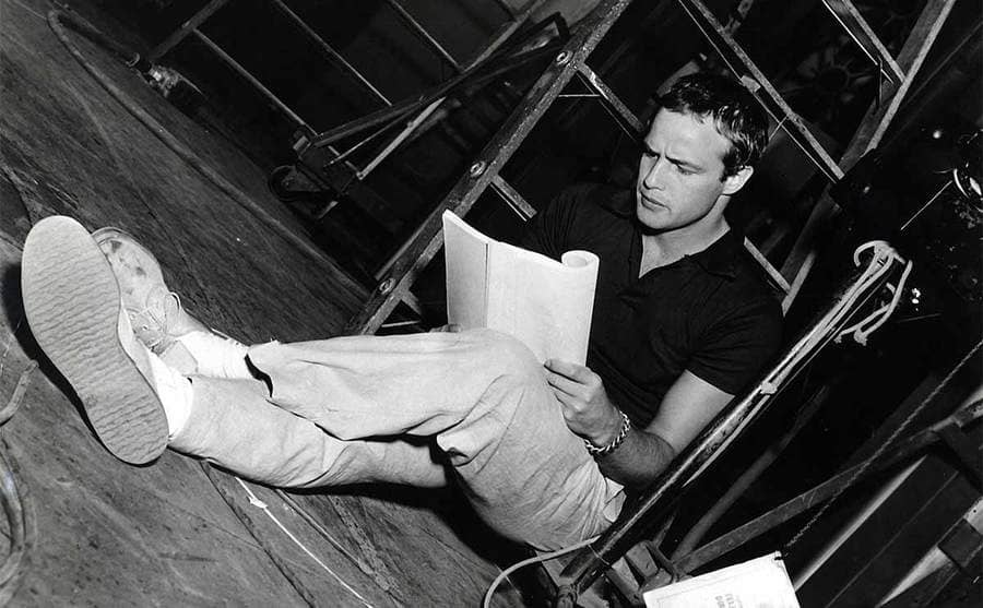 Marlon Brando sitting on the floor going over a script