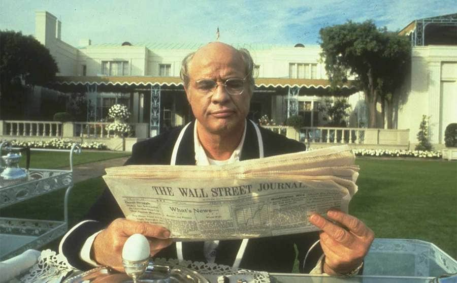 Marlon Brando reading the newspaper in the garden of a mansion with a single hardboiled egg in front of him