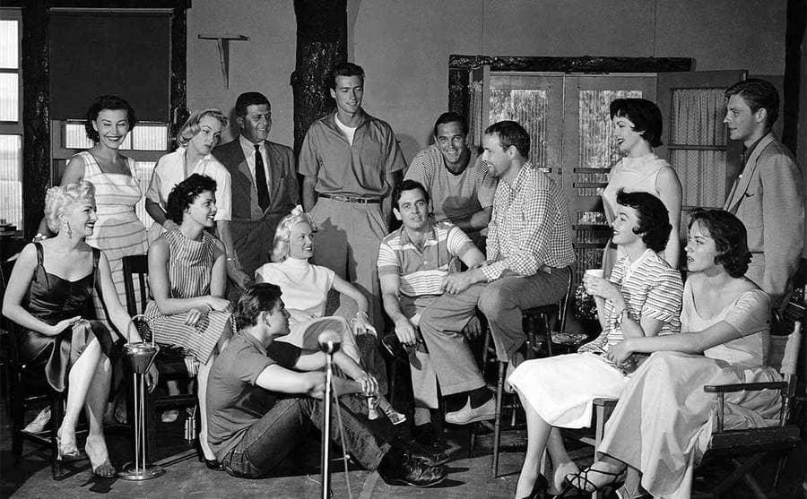 Mamie Van Doren, Clint Eastwood, David Janssen, Marlon Brando, Grant Williams, and others sitting around in a half-circle, talking