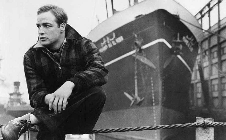 Marlon Brando sitting on a pier next to a large ship
