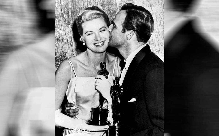 Grace Kelly receiving a kiss on the check from Marlon Brando while they are both holding Oscars