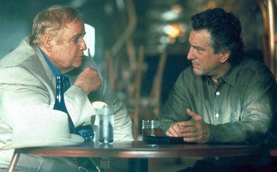 Marlon Brando and Robert De Niro sitting at a table in the bar