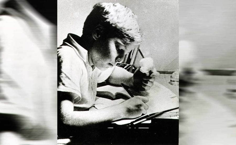 Marlon Brando as a child sitting at a table doing work and eating something