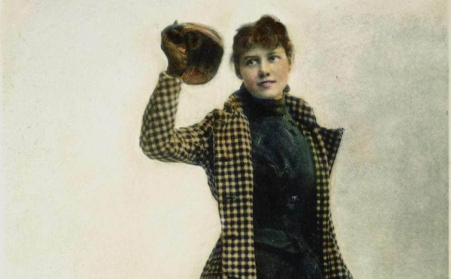 Nellie Bly standing in a trench coat