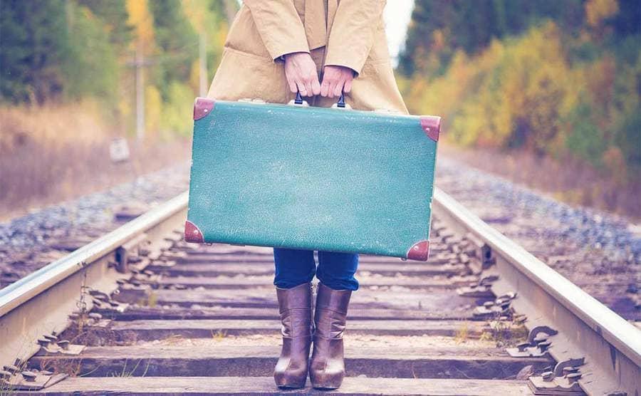 A woman holding a vintage suitcase