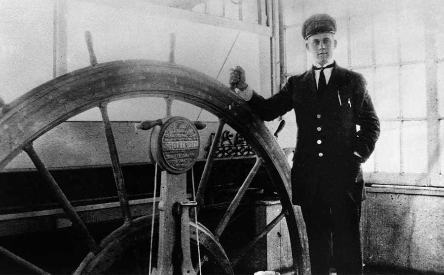 A steamship captain standing by the wheel