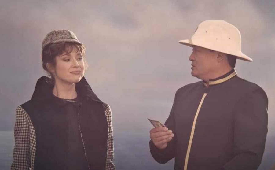Ellie Kemper as Nellie Bly and a man telling her that Elizabeth is in the lead