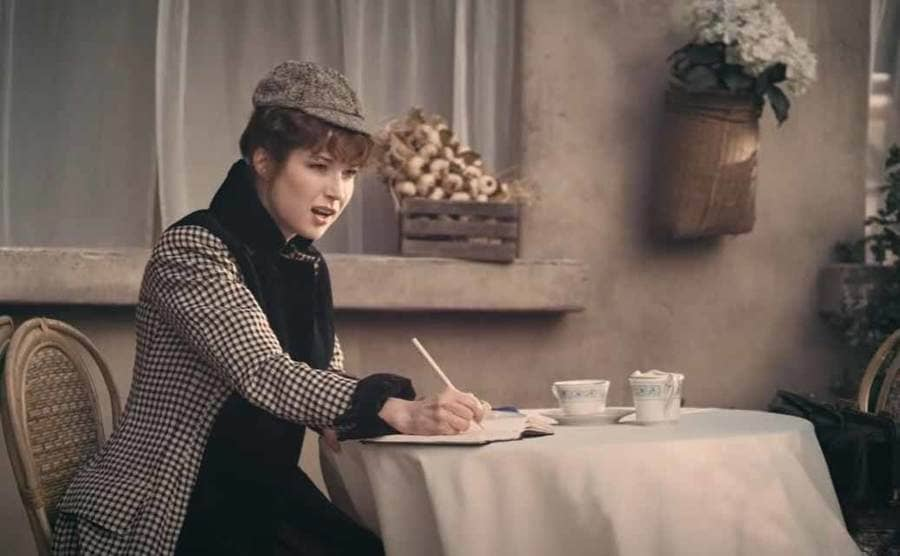 Ellie Kemper as Nellie Bly sitting at a table at a café with a cup of tea writing in her journal
