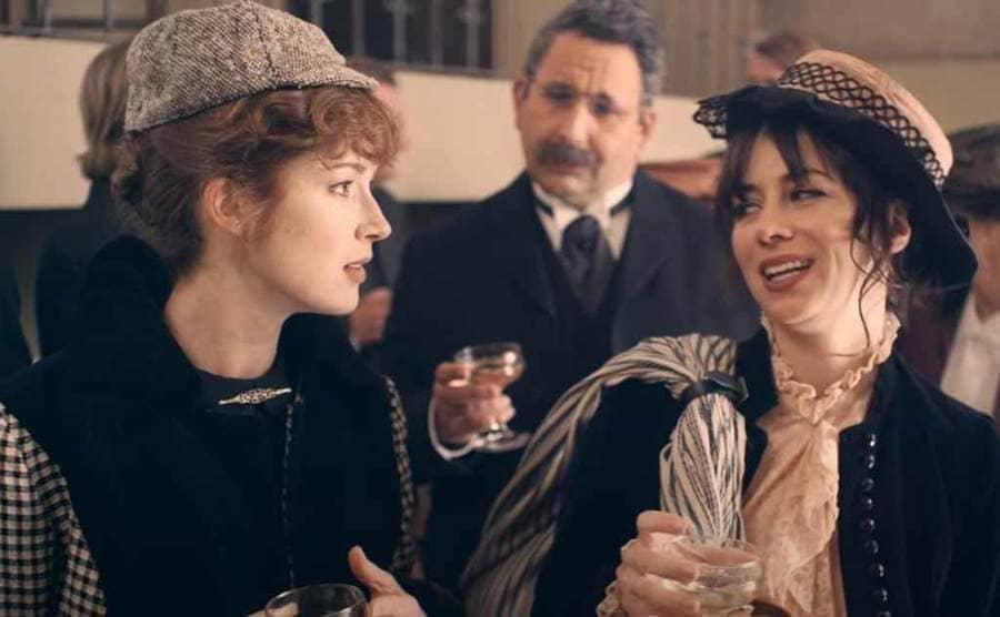 Ellie Kemper as Nellie Bly and Natasha Leggero as Elizabeth Bisland talking while having a drink