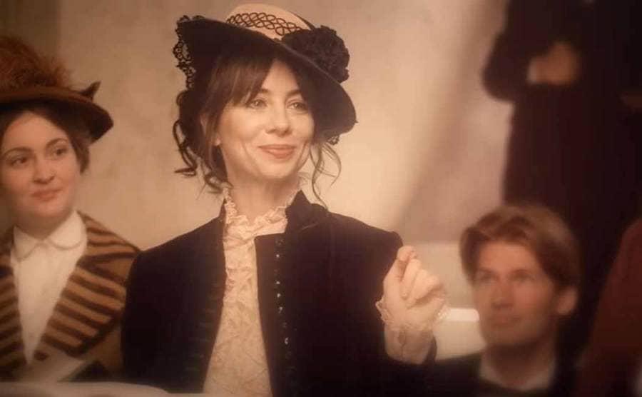 Natasha Leggero as Elizabeth Bisland reading from a book in an episode of Drunk History