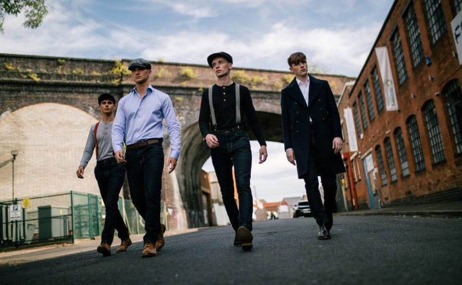 Four young men dressed in peaky blinder style clothing.