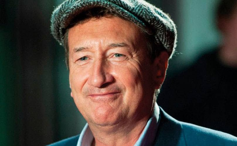 Steven Knight smiling while wearing a flat cap.