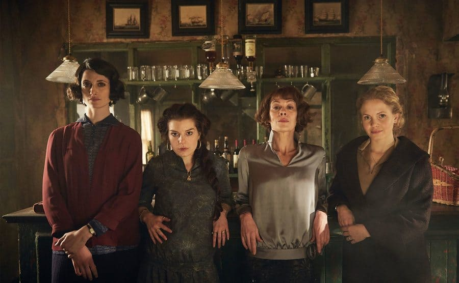 The cast of women from 'Peaky Blinders' posing in a bar.